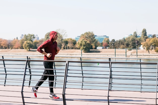 Junger athletischer mann im sweatshirt hoodie, der am park läuft