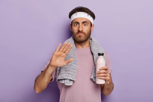 Junger athletischer mann macht ablehnungsgeste, bittet ihn nicht zu stören, gekleidet in aktiver kleidung, weißes stirnband, handtuch um den hals, hält flasche frisches wasser