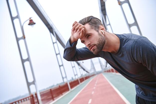 Junger athletischer mann macht eine pause während eines herausfordernden joggens im freien taking