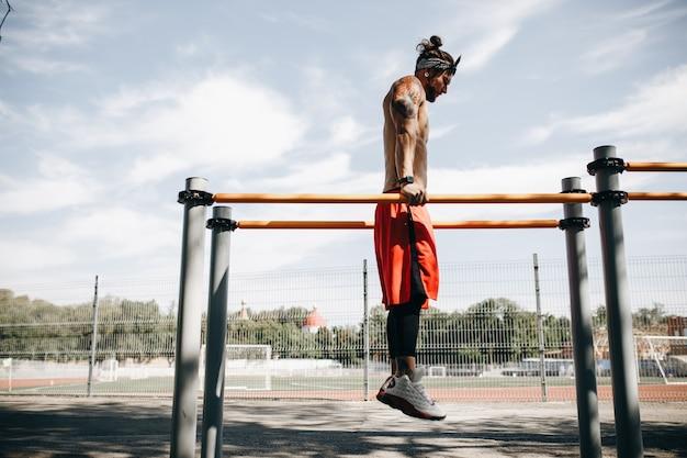 Junger athletischer mann macht einen handstand am stufenbarren auf dem sportplatz draußen