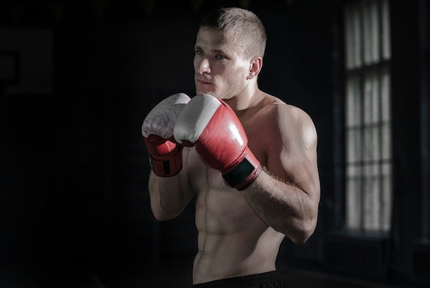 Junger athletischer mann mit boxhandschuhen und einem gestell