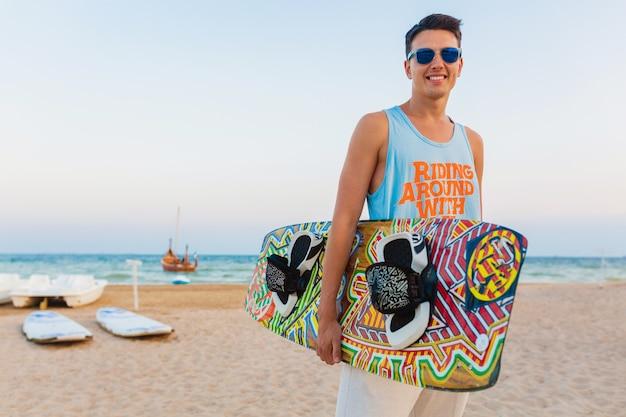 Junger athletischer mann mit kitesurfenbrett, das am strand aufgibt, der sonnenbrillen auf sommerferien trägt