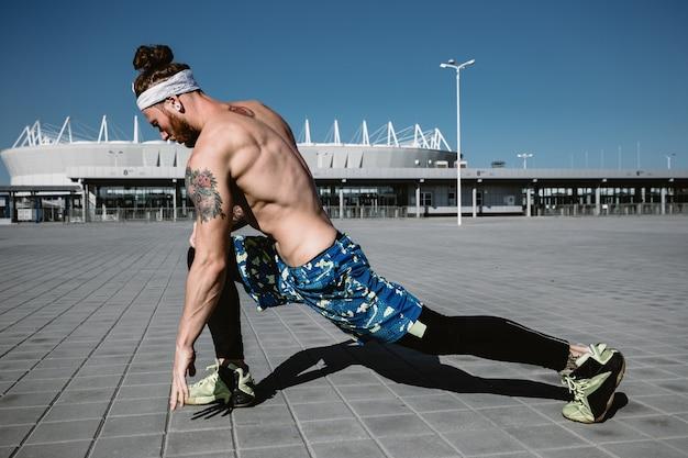 Junger athletischer mann mit nacktem oberkörper mit stirnband in schwarzen leggings und blauen shorts streckt sich an einem warmen sonnigen tag auf pflasterplatten im hintergrund des stadions.