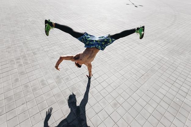 Junger athletischer mann mit nacktem oberkörper mit tätowierungen in schwarzen leggings und blauen shorts, der den trick macht, der mit einer hand auf den pflastersteinen auf der straße steht.