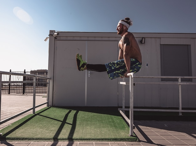 Junger athletischer mann mit nacktem oberkörper mit tätowierungen und mit stirnband in schwarzen leggings und blauen shorts macht an einem warmen sonnigen tag sportübungen auf metallzäunen.