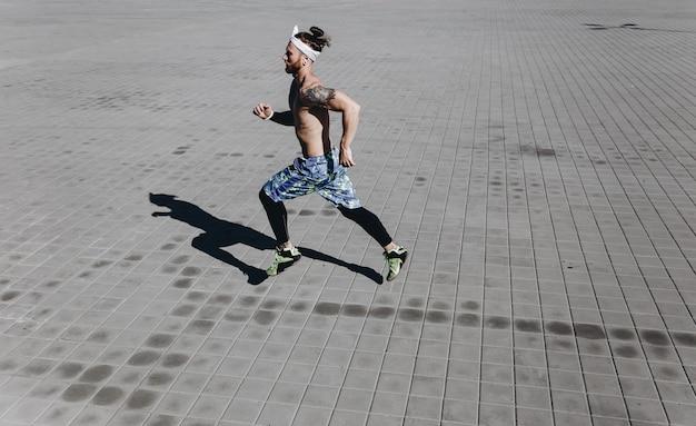Junger athletischer mann mit nacktem oberkörper mit tätowierungen und stirnband auf dem kopf in schwarzen leggings und blauen shorts läuft an einem warmen sonnigen tag auf pflastersteinen.