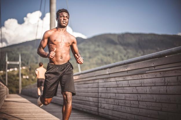 Junger athletischer schwarzer mann joggt auf der holzbrücke außerhalb der stadt.