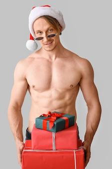 Junger athletischer weihnachtsmann mit geschenken auf grau