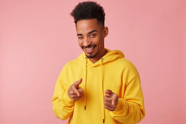 Junger attraktiver afroamerikanermann im gelben kapuzenpulli, zeigt finger nach vorne, zwinkert und sagt