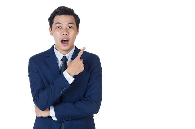 Junger attraktiver asiatischer geschäftsmann, der marineblauen anzug mit weißem hemd und krawatte trägt, lächelt und sieht überrascht aus und zeigt mit dem finger nach oben. weißer hintergrund. isoliert