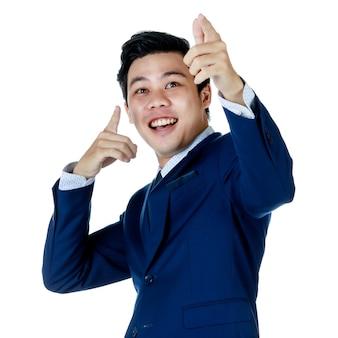 Junger attraktiver asiatischer geschäftsmann, der marineblauen anzug mit weißem hemd und krawatte trägt, zeigt seine finger auf die luft und schaut auf weißem hintergrund nach oben. isoliert