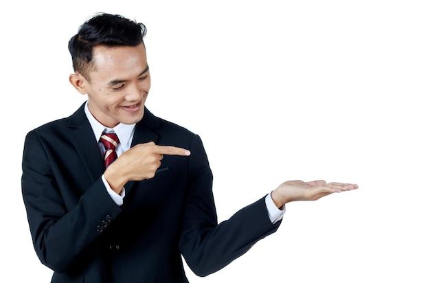 Junger attraktiver asiatischer geschäftsmann, der schwarzen anzug mit weißem hemd und krawatte trägt und lächelt und selbstbewusst aussieht, zeigt seinen finger auf eine andere hand, um ein produkt zu zeigen. weißer hintergrund. isoliert