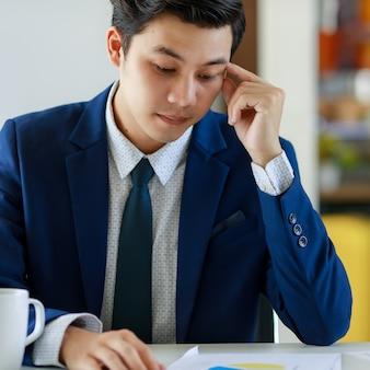 Junger attraktiver asiatischer mann, der hart arbeitet und stressig an papierkram mit frustriertem gesicht in dunkelblauem anzug im büro denkt.