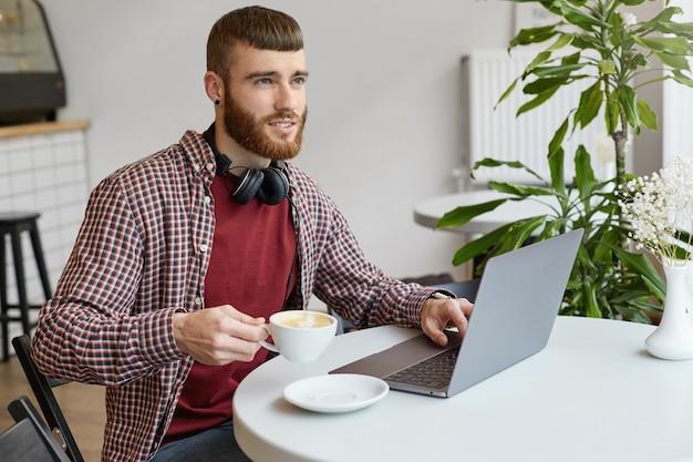 Junger attraktiver bärtiger mann des ingwers, der an einem laptop arbeitet, in einem café sitzt, in der grundkleidung trägt, breit lächelt und die arbeit genießt, wegschaut, kaffee trinkt und lächelt.