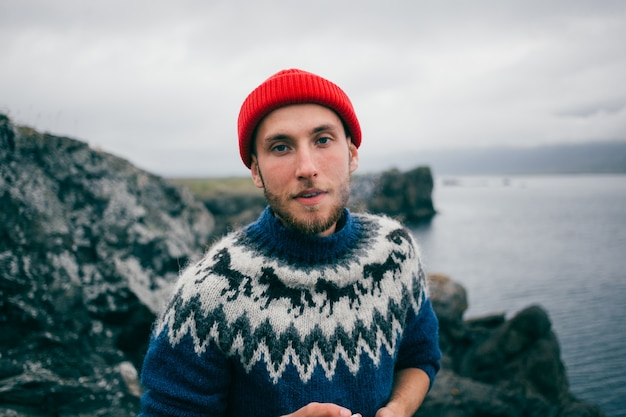 Junger attraktiver bärtiger tausendjähriger mann im roten fischer- oder matrosenmützenhut und im traditionellen blauen pullover der isländischen verzierung