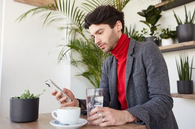 Junger attraktiver braunhaariger unrasierter mann, der im stadtcafé sitzt