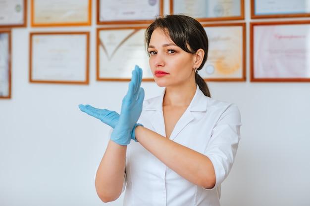Junger attraktiver brünetter arzt im weißen medizinischen mantel und in den blauen handschuhen, die das zeichen des verbots gegen die wand mit diplomen zeigen