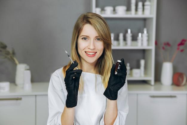 Junger attraktiver doktor mit spritze. kosmetikerin macht drinnen eine injektion. hände, die spritze und cocktail halten frau im medizinischen salon.