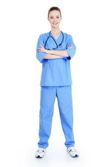 Junger attraktiver erfolgreicher weiblicher chirurg, der in der blauen uniform steht