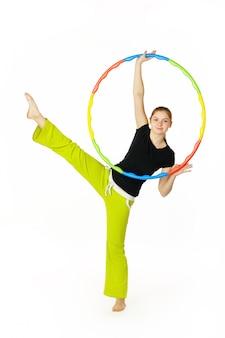 Junger attraktiver frauenfitnesslehrer, der hula hoop hält