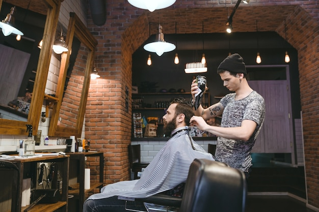 Junger attraktiver friseur mit tatoo im schwarzen hut, der die haare des mannes mit föhn im friseursalon trocknet