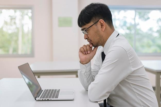 Junger attraktiver geschäftsmann, der mit computerlaptop im büro denkt