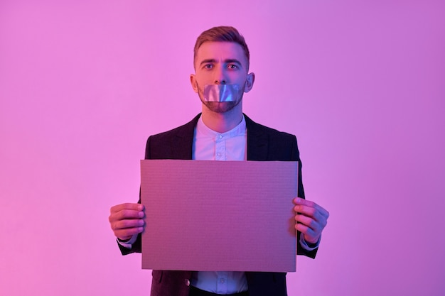 Junger attraktiver geschäftsmann im schwarzen anzug und im weißen hemd mit klebeband auf seinem mund hält pappe in seinen händen leeren raum für text lokalisiert auf neonrosa