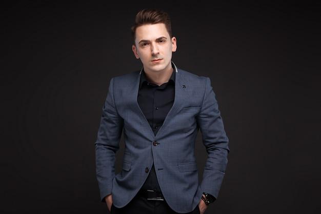Junger attraktiver geschäftsmann in der grauen jacke, teure uhr, schwarzes hemd