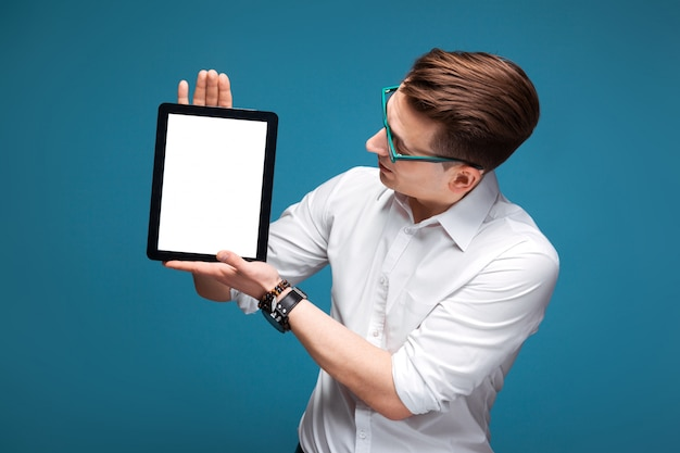 Junger attraktiver geschäftsmann in der kostspieligen uhr, in den schwarzen gläsern und im weißen hemd halten leere tablette