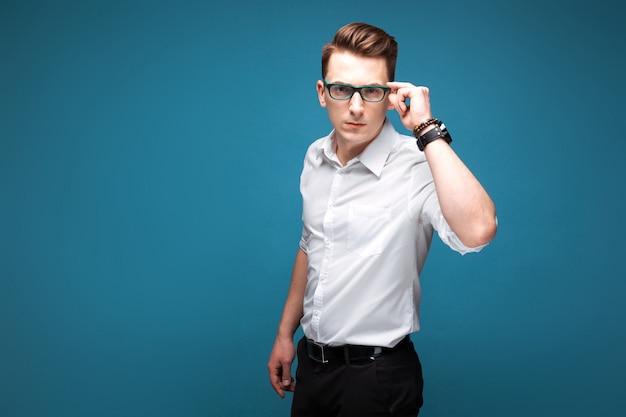 Junger attraktiver geschäftsmann in der kostspieligen uhr, in den schwarzen gläsern und im weißen hemd
