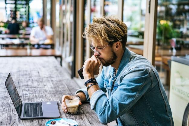 Junger attraktiver geschäftsmann in einem café arbeitet für einen laptop, trinkt kaffee.