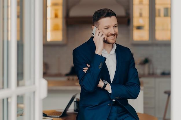 Junger attraktiver geschäftsmann in formellem anzug, der am telefon spricht und lächelt, wenn er gute nachrichten hört, sich auf den tisch im wohnzimmer stützt, smartphone hält und projektergebnisse diskutiert. geschäftskonzept