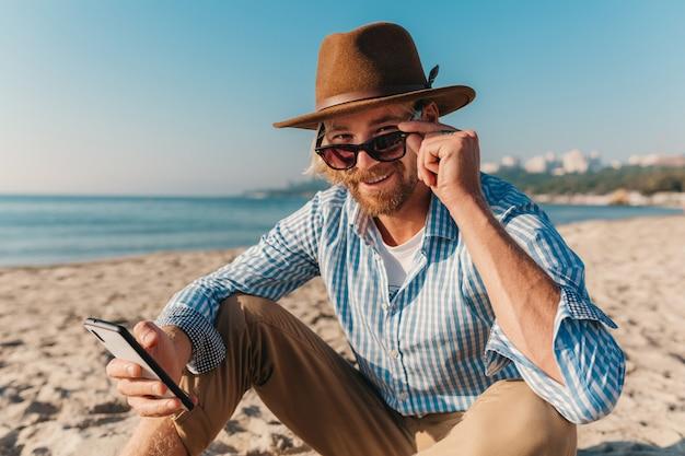 Junger attraktiver hipster-mann, der auf strand durch meer in den sommerferien sitzt