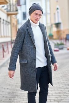 Junger attraktiver hipster-mann, der einen grauen mantel, einen weißen pullover und schwarze jeans trägt, die in der straße gehen