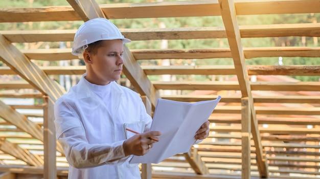 Junger attraktiver ingenieur in einem weißen helm überprüft den dachrahmen, konzeptkarriere-architekt.