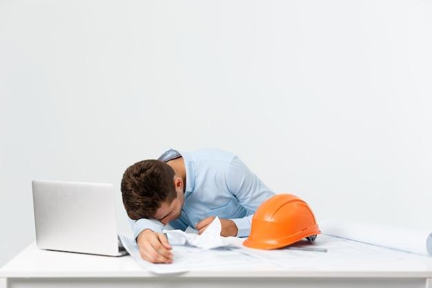 Junger attraktiver ingenieursmann, der sich am arbeitsplatz müde fühlt.
