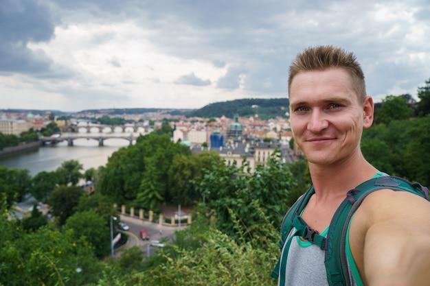 Junger attraktiver kerl, der selfie mit landschaftsblickbrücken auf moldau in der tschechischen republik prag nimmt.