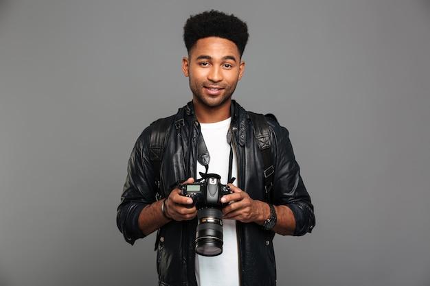 Junger attraktiver lächelnder afroamerikanischer mann, der die digitalkamera, schauend hält
