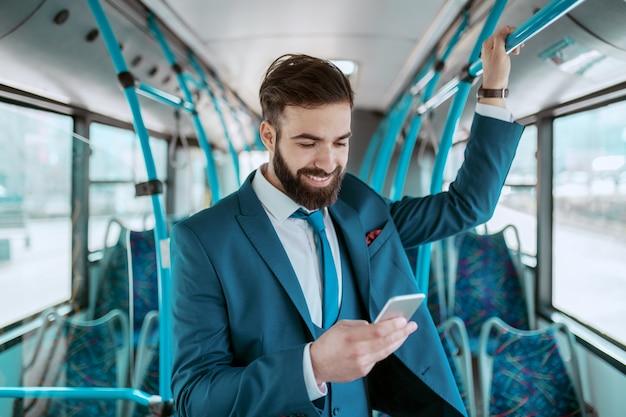 Junger attraktiver lächelnder geschäftsmann im blauen anzug, der im öffentlichen verkehr steht und smartphone für sms oder lesung der nachricht verwendet.