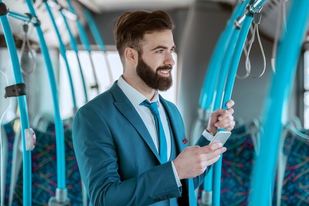 Junger attraktiver lächelnder geschäftsmann im blauen anzug, der in den öffentlichen verkehrsmitteln steht und smartphone für sms oder lesen der nachricht beim schauen durch trogfenster verwendet.