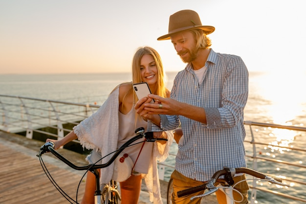 Junger attraktiver lächelnder glücklicher glücklicher mann und frau, die auf fahrrädern mit smartphone reisen, romantisches paar am meer bei sonnenuntergang, boho-hipster-stil-outfit, freunde, die spaß zusammen haben