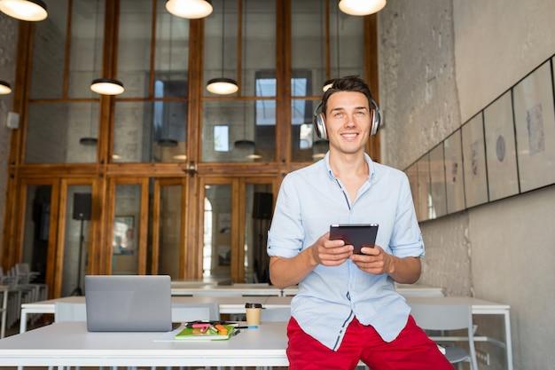Junger attraktiver lächelnder glücklicher mann, der tablette verwendet, die musik auf drahtlosen kopfhörern hört