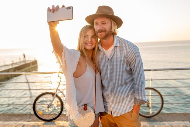 Junger attraktiver lächelnder glücklicher mann und frau, die auf fahrrädern reisen, die selfie-foto auf telefonkamera machen, romantisches paar am meer auf sonnenuntergang, boho-hipster-art-outfit, freunde, die spaß zusammen haben