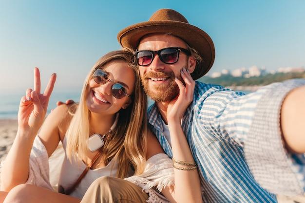 Junger attraktiver lächelnder glücklicher mann und frau in der sonnenbrille, die auf sandstrand sitzt, der selfie foto macht