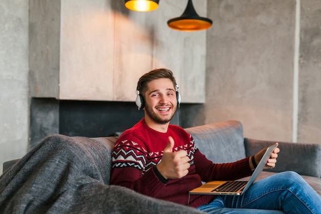Junger attraktiver lächelnder mann auf sofa zu hause im winter in kopfhörern, trägt roten strickpullover, arbeitet am laptop, freiberufler, glücklich, positiv, zeigt daumen nach oben