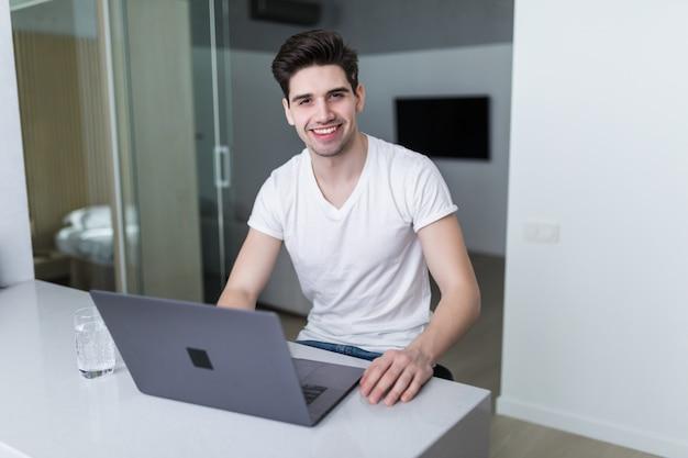 Junger attraktiver lächelnder mann sucht an seinem laptop und sitzt zu hause