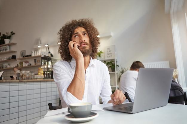 Junger attraktiver langhaariger geschäftsmann, der konversation am telefon während der arbeit außerhalb des büros mit laptop, tasse kaffee im mittagessen arbeitend hat