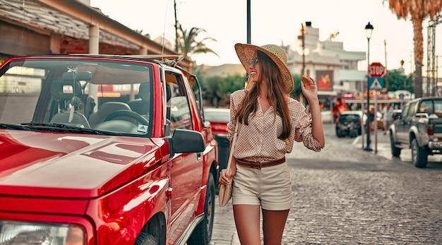 Junger attraktiver mädchentourist in einer bluse, einem strohhut und einer sonnenbrille, die die straßen der stadt gehen. das konzept des tourismus, reisen.