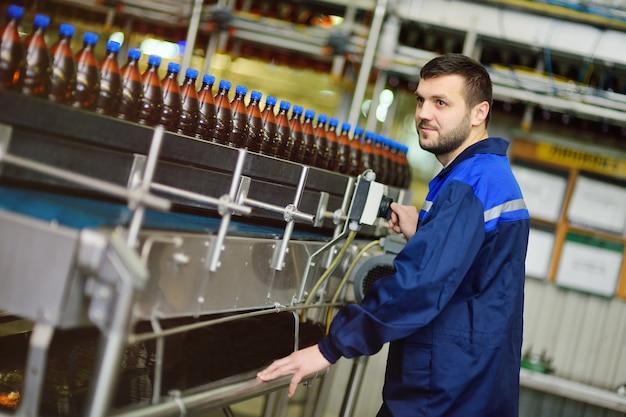 Junger attraktiver männlicher brauer oder brauereiarbeiter in der uniform vor dem hintergrund eines förderbandes mit plastikflaschen des bieres