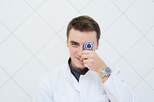 Junger attraktiver männlicher doktordermatologe mit dermatoscope in der hand